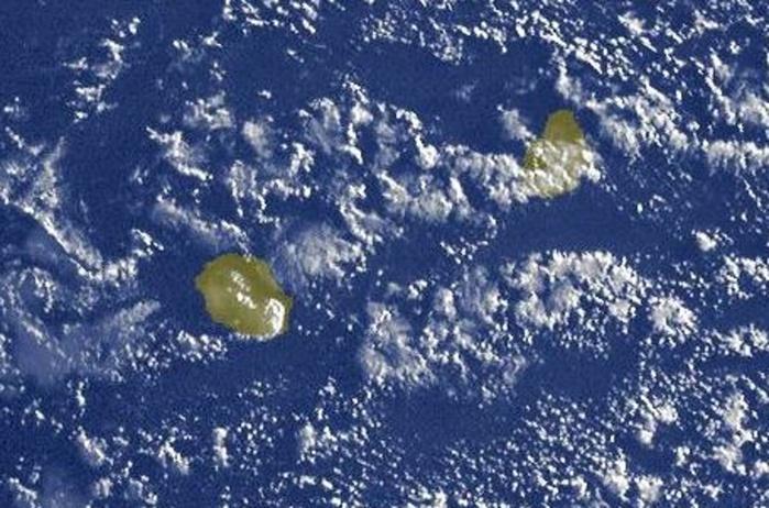 Photo satellite de 7h15. Des nuages poussés par les alizés circulent au large des côtes est réunionnaises. Des nuages sont accrochés aux pentes du volcan.